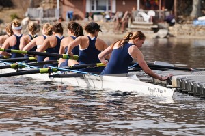 Members of the Women's Rowing Team push off from the dock at the boathouse on Coventry Lake in their new racing shell, named in honor of retired psychology professor Sam Witryol. Photo by Peter Morenus