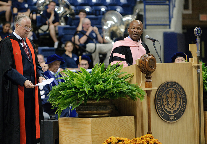 <p>Lee Melvin, interim vice president for enrollment management, right, presents the new class to Provost Peter Nicholls during the Convocation ceremony at Gampel Pavilion on Aug. 31. Photo by Peter Morenus</p>