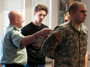 <p>Sergeant First Class John Maynard, left, and Cadet Chris Edam demonstrate various military conventions to help students Daniel Seigerman and Cayla Buettner prepare for an upcoming Connecticut Repertory Theatre production. Photo by Frank Dahlmeyer</p>