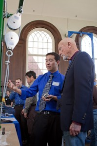 "<p>Mechanical Engineering senior Erik Kong discusses a bearing testing unit with alumnus Richard Gamble (Electrical and Mechanical Engineering, '49). Mr. Gamble, now retired, is a former president and CEO of Colt Industries and a former executive with Hamilton Standard (now Hamilton Sundstrand).  Erik and fellow student Stephen Symski (ME) developed the ""Metering Tank Bearing Failure & Design Analysis"" project for Rogers Corporation. The project captured second prize and $1,000 in a juried competition among Mechanical Engineering seniors. The students presented their prototype during the School of Engineering's Senior Design Demonstration day held in the Wilbur Cross building on Friday, April 30. Photo by Christopher LaRosa</p>"