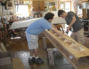 <p>Undergraduates Peter Omdahl and Jon Turban add a construction platform to pieces that will become the strongback, or the bottom, of the boat. Photo by Bill Armitage </p>