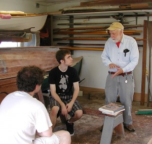 <p>Photo of two Avery Point undergraduates doing a boatbuilding internship with Bill Armitage of the John Gardner chapter of the Traditional Small Craft Association. Photo by Christine Buckley </p>