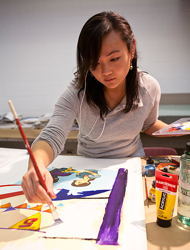 <p>Sherry Wong, illustration major works on a illustration celebrating the 50th Anniversary of the Peace Corps. Photo by Sean Flynn</p>