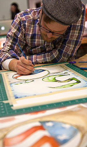 "<p>Dylan Fedora works in watercolors to create his commemorative poster which will be among those displayed on campus next spring during ceremonies observing the Peace Corps' official birthday in March.  Finished poster will all be 18"" x 24"", yet they are all very different in texture, design, and message.  </p>"