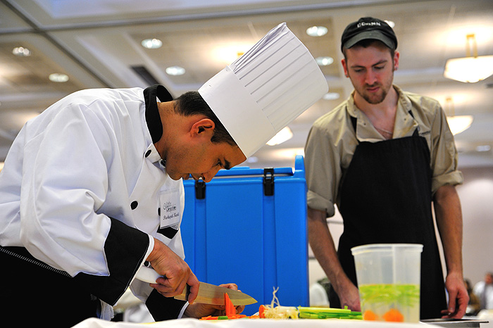 <p>Pashupati Karki, left, of the South Marketplace prepares garnishes as he finishes his entry in the culinary competition.Photo by Peter Morenus</p>
