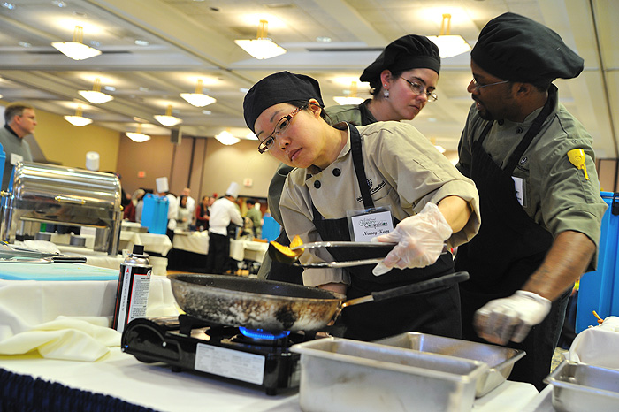 <p>Nancy Kam of the Union Street Market prepares squash as she competes with chefs from around campus.  Photo by Peter Morenus</p>