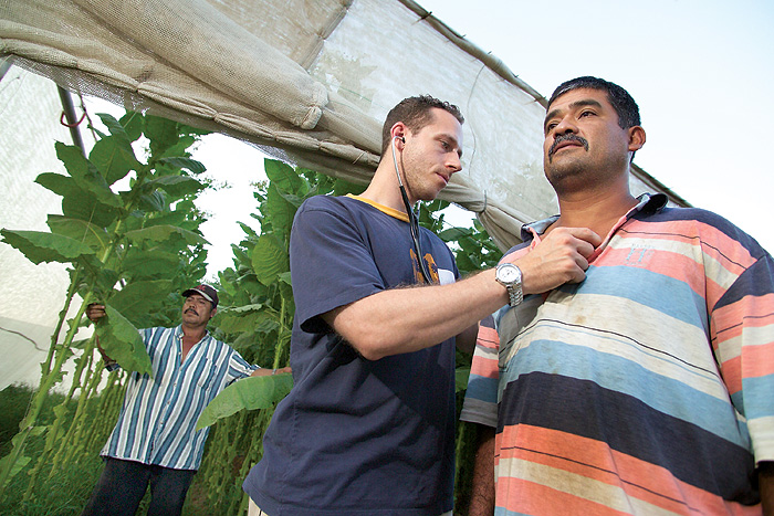 <p>Migrant worker Homero Gonzalez gets a physical exam from medical student Christopher Binette,'08 SOM, at a clinic for migrant farm workers run by UConn Health Center medical students at one of the tobacco farms in Connecticut. Photo by Al Ferreira</p>
