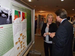 M.P.H. student Cheryl Marenick discusses her poster presentation, about disparities relative to elderly patient falls, with Richard Fortinsky in the Keller Lobby. (Chris DeFrancesco/UConn Health Center Photo)