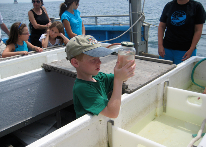An eight-year-old participant in a two-hour cruise on Long Island Sound looks at various types of plankton netted from the Sound. The cruise was offered by the Connecticut State Museum of Natural History. (UConn File Photo)