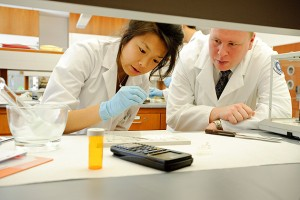 Students hand fill capsules at the dosage forms lab in the Pharmacy/Biology Building. (Peter Morenus/UConn Photo)