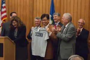 UConn President Susan Herbst and UConn Board of Trustees President Larry McHugh present Jackson Laboratory CEO Dr. Edison Liu with a UConn t-shirt at the governor's press conference at the Capitol on September 30, 2011. (Tina Encarnacion/UConn Health Center Photo)