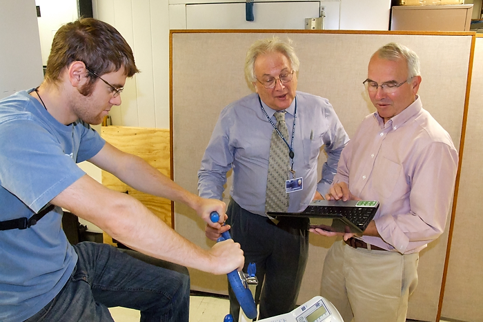 From left: Graduate student Drew Seils, Dr. Martin Cherniack, and Tim Morse demonstrate an exercise bike test in the Ergonomics Technology Center. (Chris DeFrancesco/UConn Health Center Photo)