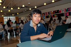 Pei-Kang Wu works on his laptop in the School of Business Café. (Ariel Dowski '14 (CLAS)/UConn Photo)