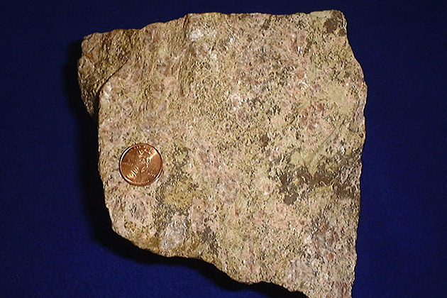 Rare earth ore, shown with a United States penny for size comparison. (Wikipedia)