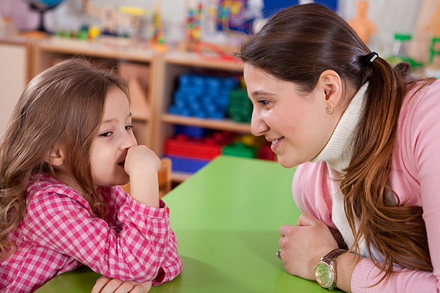 Teacher talking with little girl.