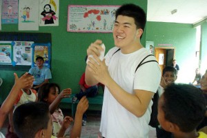 Brian Yu '€™13 (BUS) plays with the kids at an orphanage in Honduras before setting up triage as a part of their medical clinic, where they taught patients how to take care of their teeth and floss.