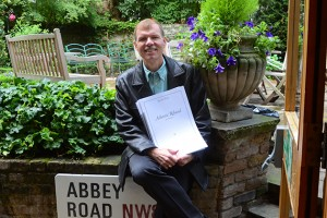 Music professor Kenneth Fuchs in the Abbey Road Studios garden in London, holding a score of his composition in honor of the S.S. United States. (Photo courtesy of Kenneth Fuchs)