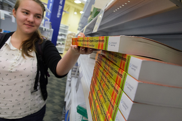 Shea Westlake '16 (CLAS) takes a textbook off the shelf at the UConn Co-op. (Ariel Dowski '14 (CLAS)/UConn Photo)