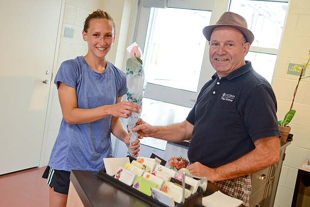 Jim Palmieri, manager of UConn Blooms in the Floriculture Building, gives Colleen Jost '14 (ENG) a free rose. (Ariel Dowski '14 (CLAS)/UConn Photo)