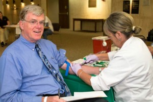 Dr. Richard Everson, himself a cancer researcher, is now also a study participant, as phlebotomist Norah Farris takes a blood draw. (Tina Encarnacion/UConn Health Center Photo)
