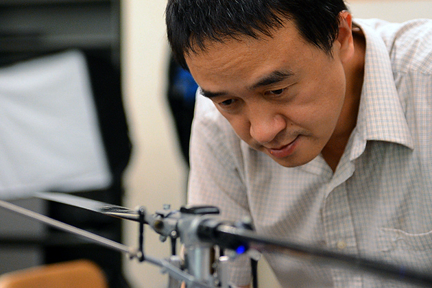 Chengyu Cao, assistant professor of mechanical engineering, with an unmanned vehicle in the lab. (Bret Eckhardt/UConn Photo)