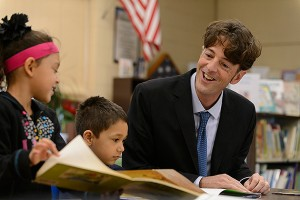 Michael Coyne, associate professor of educational psychology, encourages a young reader. (Peter Morenus/UConn Photo)