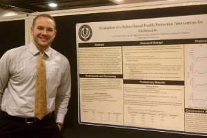 Scott McCarthy stands with a poster outlining his research. (Neag School of Education photo)