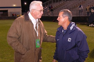 Former Huskies men's basketball coach Dee Rowe congratulates head coach Len Tsantiris '77 (ED) on earning his 500th career win after the women's soccer team defeated Rutgers 3-1 in the first round of the Big East Tournament on Thursday. (Ken Best)
