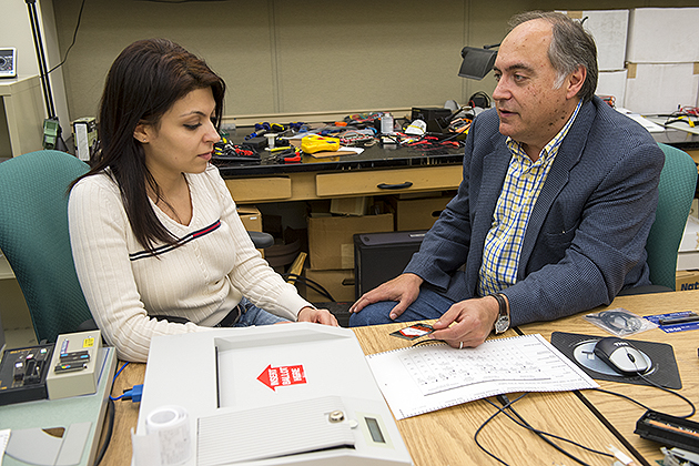 Alexander Shvartsman, professor of computer science & engineering, looks over electronic voting equipment with Ph.D. student Seda Davtyan. (Peter Morenus/UConn Photo)