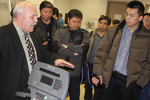 William Kraemer, professor of kinesiology in the Neag School of Education (left), explains the equipment in UConn's Human Performance Lab to the delegation from China's General Administration of Sports. (Shawn Kornegay/UConn Photo)