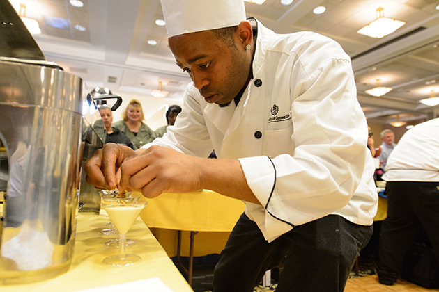 Sterling Townes of South Marketplace puts the finishing touches on part of his team's entry during the Boiling Point competition of the 13th annual Culinary Olympics held at Rome Ballroom on Jan. 17, 2013. (Peter Morenus/UConn Photo)