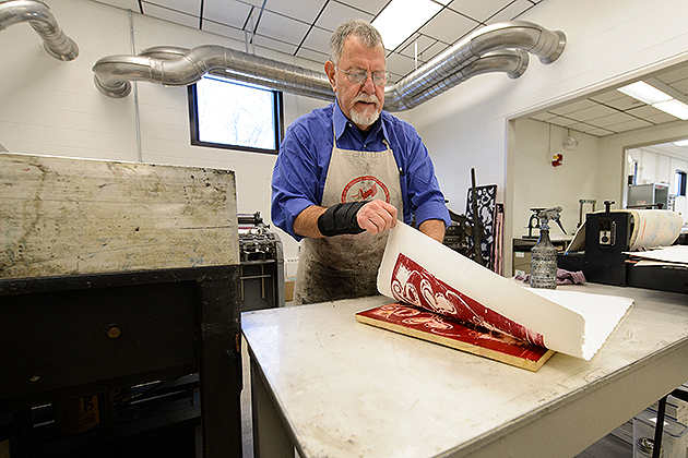 Gus Mazzocca, professor emeritus of art and art history, makes a print at the new printmaking facility at the Bishop Center. (Peter Morenus/UConn Photo)