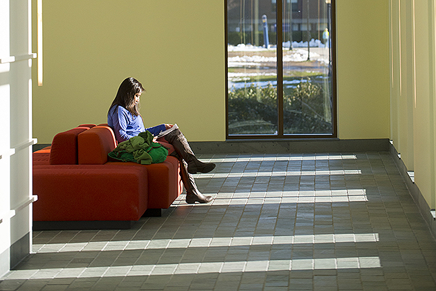 A student sits reading in a hallway in Laurel Hall. The building includes such features as energy-saving window glazing. (Peter Morenus/UConn Photo)