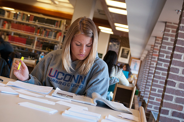 Female student wearing a UConn sweatshirt, studying at a table in the Cue Building (Center for Undergraduate Education) on March 27, 2012. (Al Ferreira for UConn)