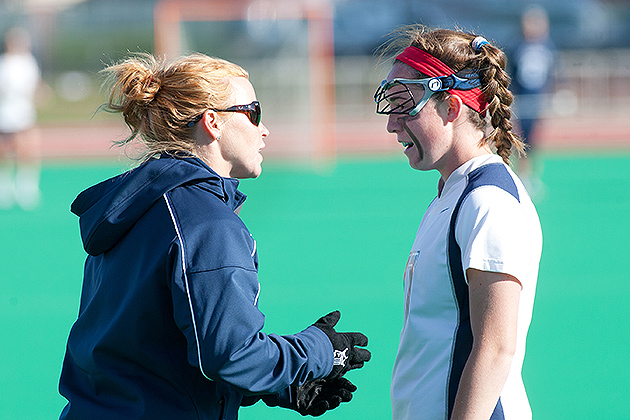 Lacrosse head coach Katie Woods (left) gives instructions to a player. (Steve Slade '89 (SFA) for UConn)
