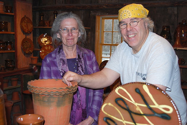 Suzy Staubach, head of General Books at the UConn Co-op, with master potter Guy Wolff in his studio. Wolff's craftsmanship is the topic of a new book by Staubach and an exhibit at Homer Babbidge Library. (Suzanne Zack/UConn Photo)