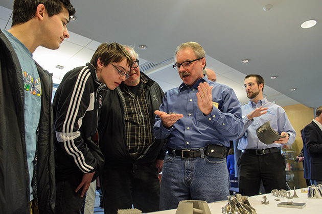 Howard Ellis, lab coordinator for computer science and engineering at UConn, right, explains how metal parts are created by additive manufacturing. (Ariel Dowski '14 (CLAS)/UConn Photo)