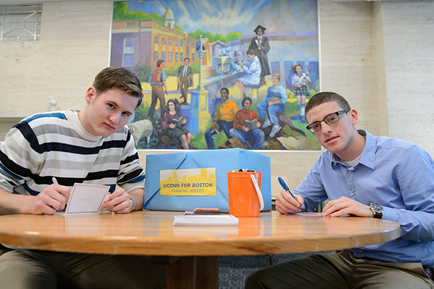Austin Dodd '15 (CLAS), left, and Justis Lopez '14 (ED) write notes to Boston area first responders at the Student Union. (Peter Morenus/UConn Photo)