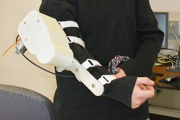 Brian Coleman'13 (ENG) developed a robotic arm that can be used by astronauts to prevent muscle loss in zero gravity. (Cathleen Torrisi/UConn photo)