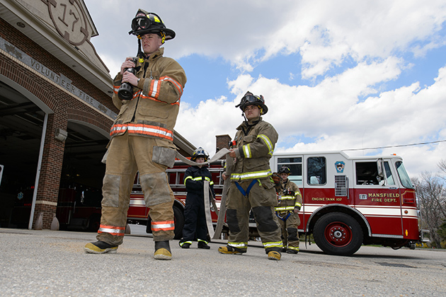 Student volunteer firefighters from UConn and Eastern Connecticut State University practice pulling a hose from an engine at the Mansfield Fire Department alongside veteran firefighter John Levasseur, third from left. (Peter Morenus/UConn Photo)