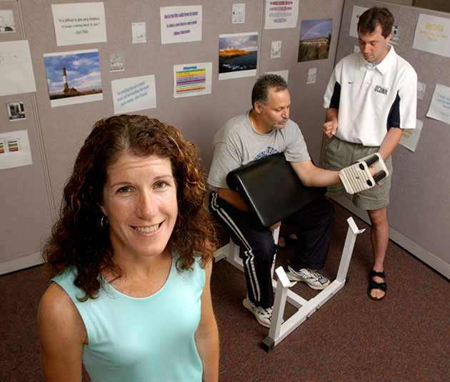 Linda Pescatello, professor of kinesiology, with a test subject and spotter demonstrating a weight training exercise. (File photo)