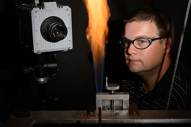 Michael Renfro, associate professor of mechanical engineering, observes a flame experiment in his lab. (Peter Morenus/UConn Photo)