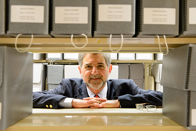 Paul Herrnson, executive director of the Roper Center for Public Opinion Research with boxes of the center's data on July 31, 2013. (Peter Morenus/UConn Photo)