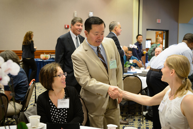 Provost Mun Choi, standing, greets, Rachel Burns, right, assistant clinical professor of pathobiology, and Deborah Shelton, professor of nursing at the new faculty orientation session held at Rome Ballroom on Aug. 23, 2013. (Peter Morenus/UConn Photo)