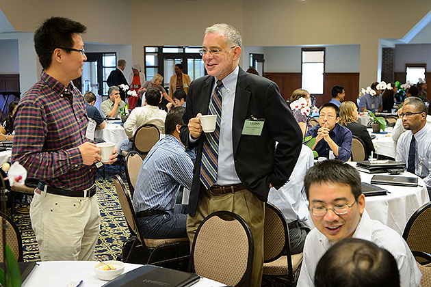 Jeremy Teitelbaum, dean of liberal arts and sciences, right, speaks with Song Han, assistant professor of computer science at the new faculty orientation session held at Rome Ballroom on Aug. 23, 2013. (Peter Morenus/UConn Photo)