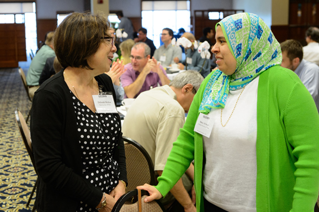 Deborah Shelton, left, professor of nursing, and Sahar Al Seesi, postdoctoral fellow in computer science and engineering, speak at at the new faculty orientation session. (Peter Morenus/UConn Photo)