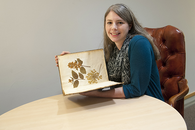 Jessica Linker, a graduate student fellow at the Humanities Institute, with a woman's herbarium from the 1850s. Linker is studying female scientists in the 18th and 19th centuries. (Sean Flynn/UConn Photo)