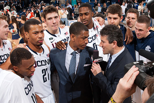 The men's basketball team surrounds head coach Kevin Ollie as he speaks with Andy Katz of ESPN after the Huskies' 66-58 upset win over No. 6 Syracuse at the XL Center in Hartford on Feb. 13, 2013. The win was one of the major highlights of Ollie's successful first season leading the squad. (Steven Slade '89 (SFA) for UConn)