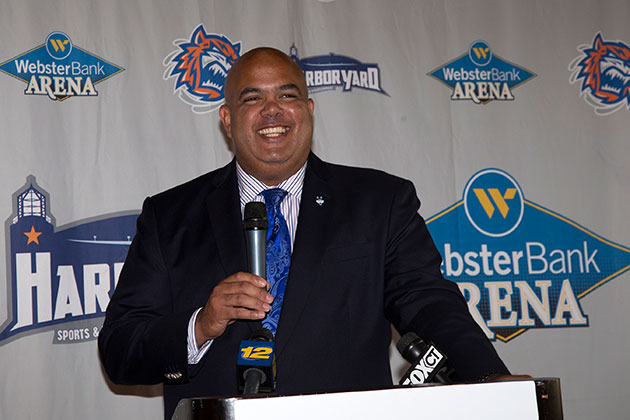 UConn athletics director Warde Manuel takes the podium during a press event on Oct. 7, 2013 announcing that the men's and women's basketball teams will each play a games in Bridgeport during the 2013-2014 season. (Stephen Slade '89 (SFA) for UConn)