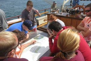 A crew member points to features on a nautical chart of Fishers Island Sound, which includes the Avery Point campus. Nautical charts are specialized tools used for navigation, published by NOAA. (Nathaniel Trumbull/UConn Photo)